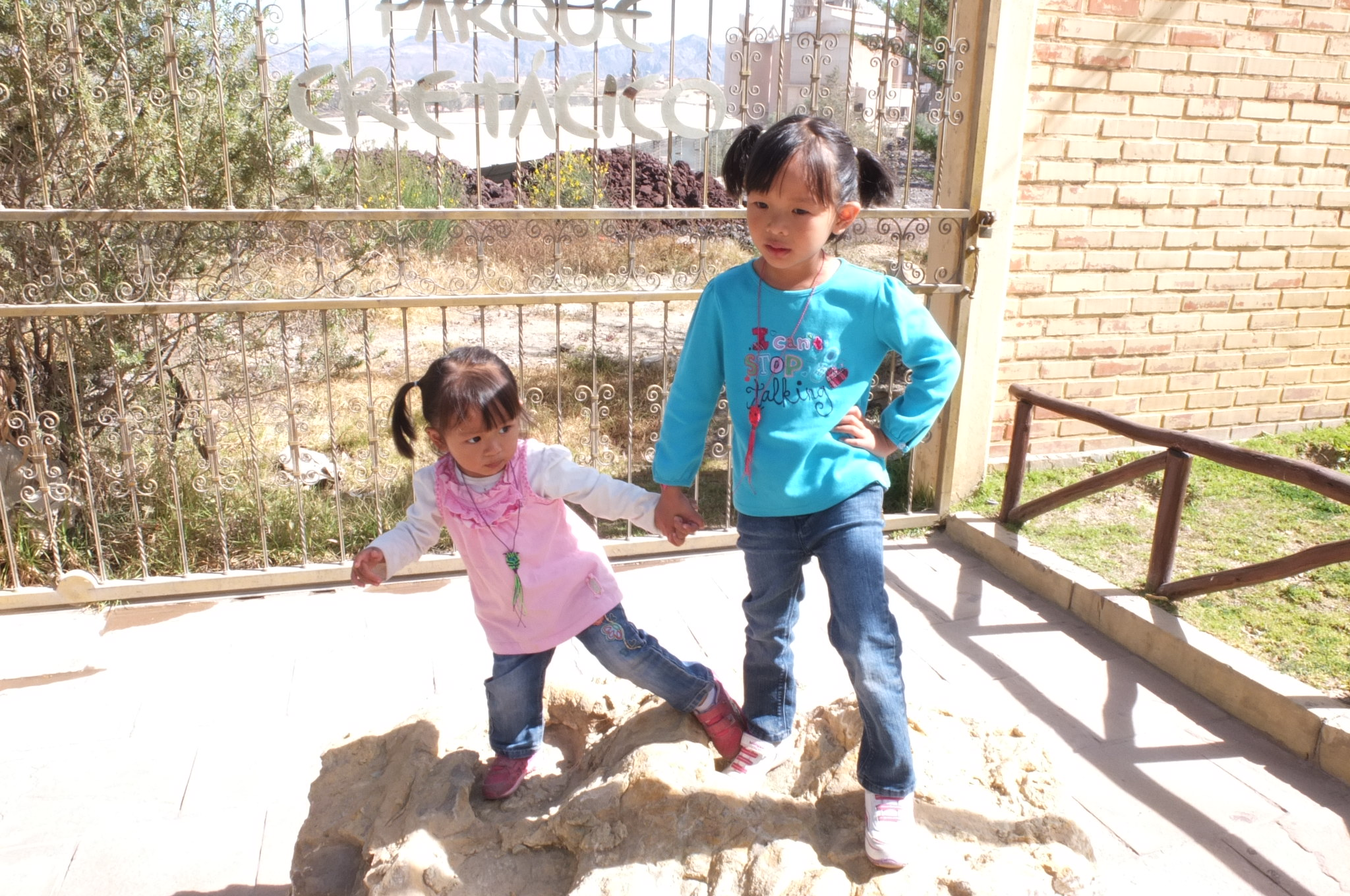 Kaylee and Talia stepping into a baby dinosaur footprints!