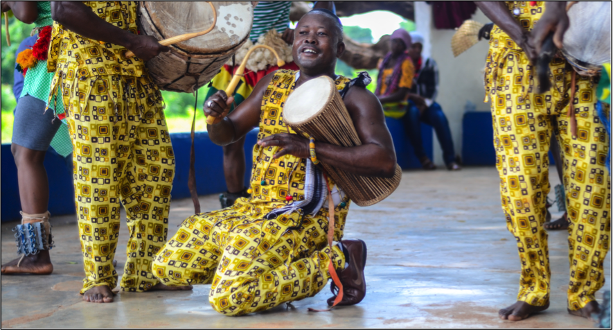 "a local playing the ""talking drum"""