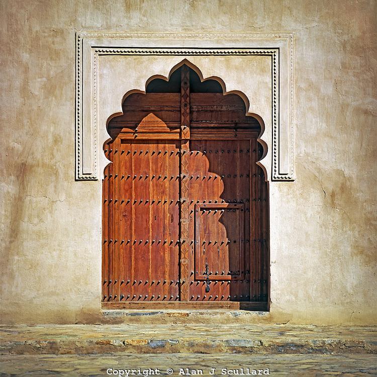 Ornate archway and wooden door in Birkat Al-Mawz Fort in Oman
