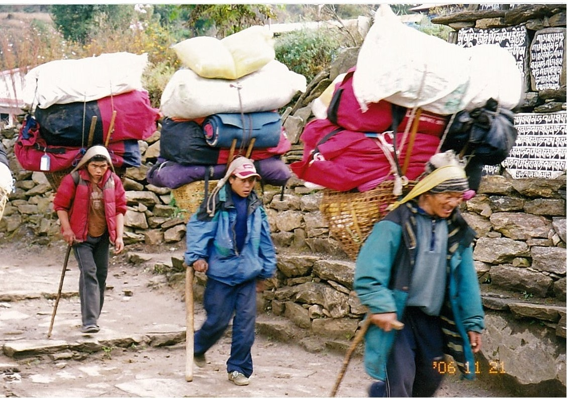 Sherpas carrying loads on their backs.