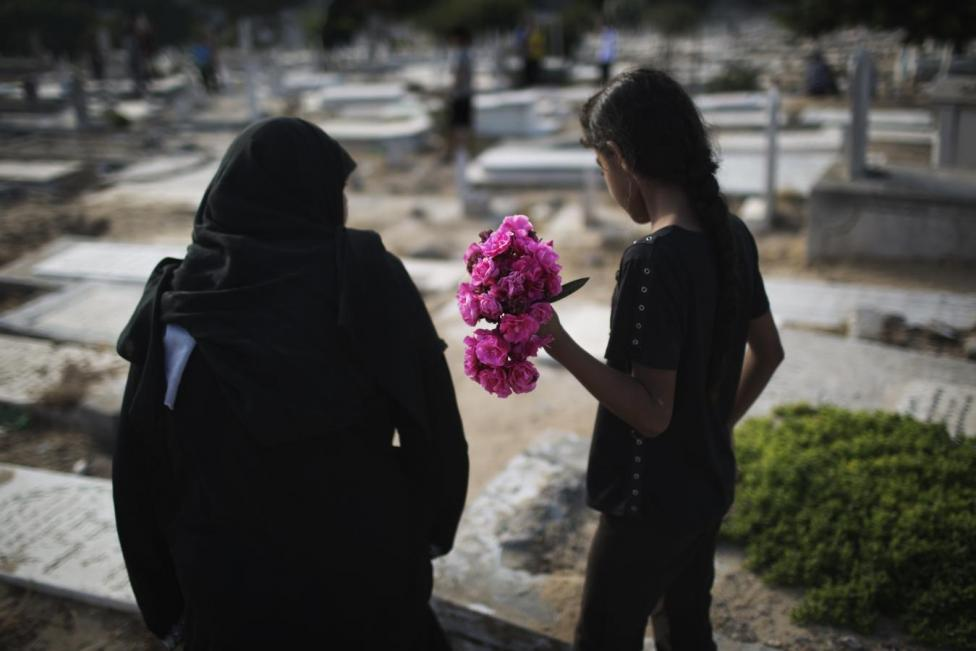 In Palestine, visiting the cemetery after Eid prayers (Reuters)