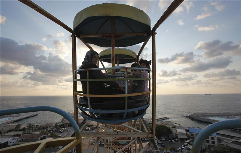 A Muslim family enjoys a ride on a ferris wheel at an amusement park during Eid al-Fitr in Beirut (Cynthia Karam)