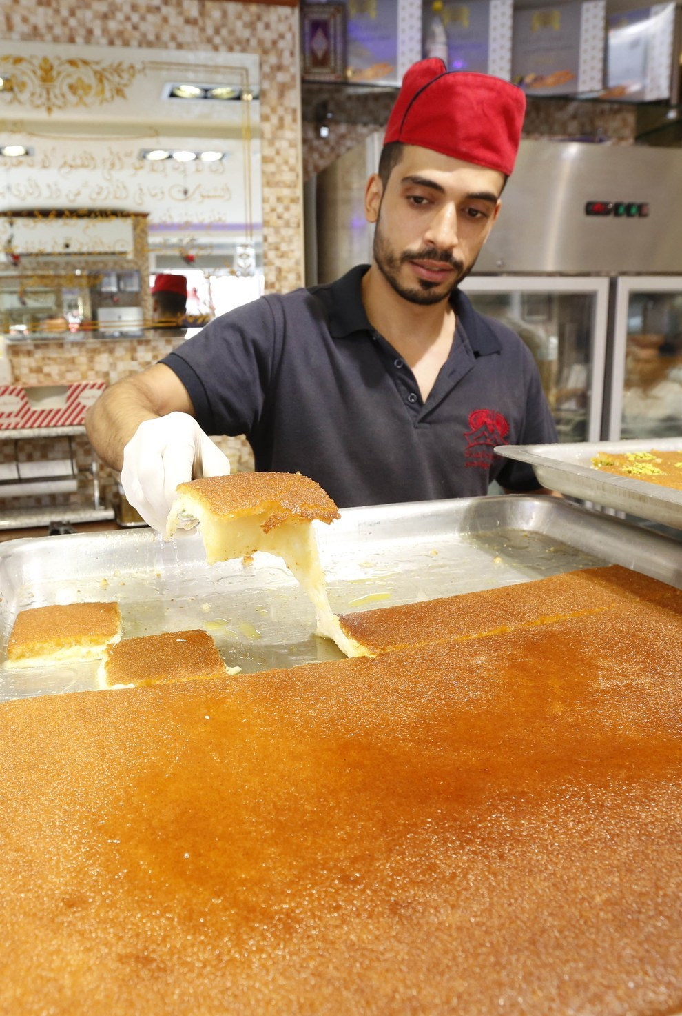 A Syrian café employee dishes out 'Kunafeh' a traditional sweet made with cheese, a dessert popular during Eid. relatives or going (Anwar Amro, Getty Images)